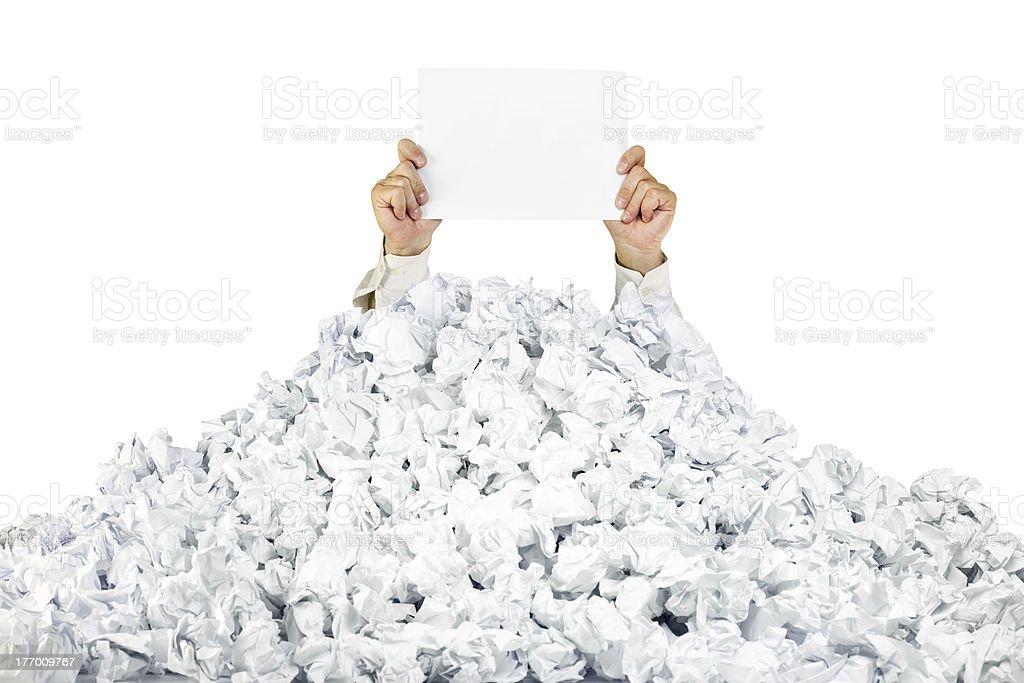 Person under crumpled pile of papers with a blank page stock photo
