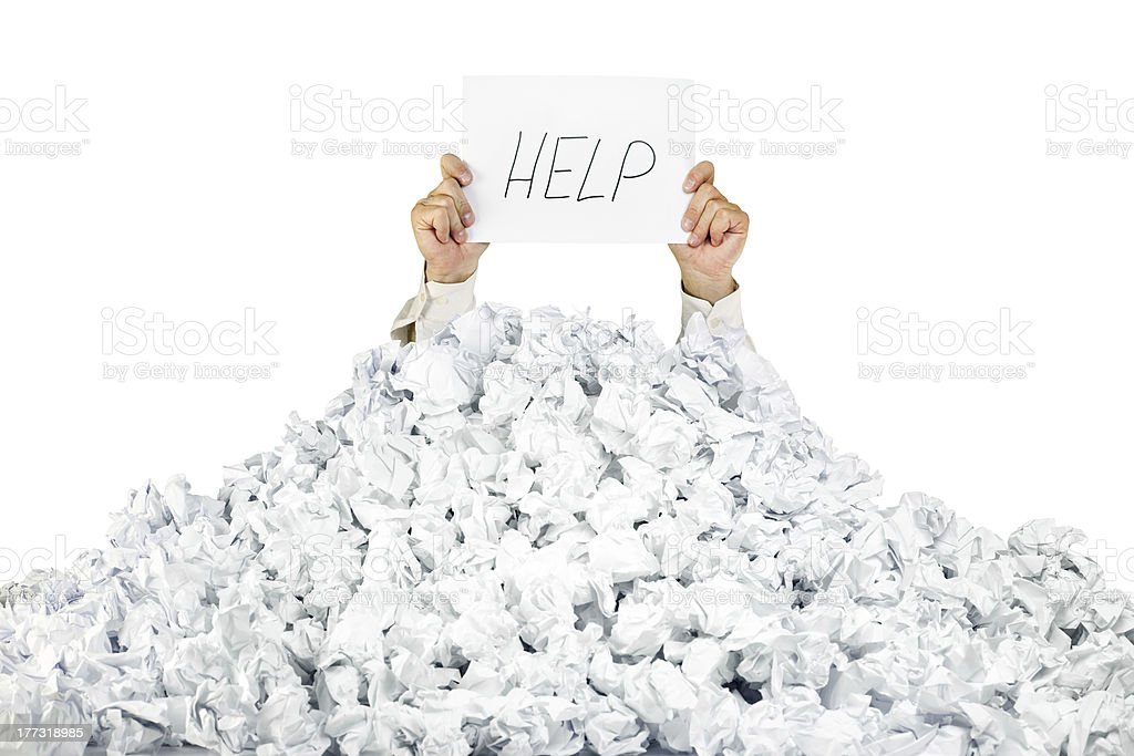 Person under crumpled pile of papers with a help sign stock photo