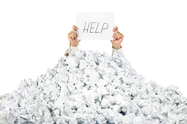 person under crumpled pile of papers with a help sign - gömülü stok fotoğraflar ve resimler