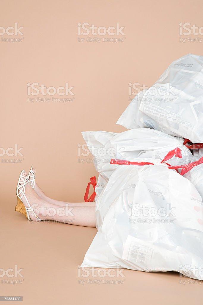 Eine person unter einem Haufen Müll Taschen Lizenzfreies stock-foto