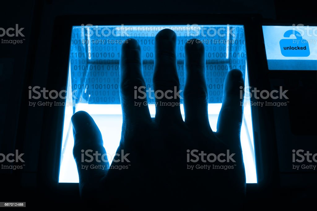person unlocks a computer on a divice with his fingerprints stock photo