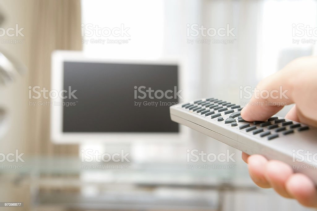 A person using a remote controller on their television stock photo