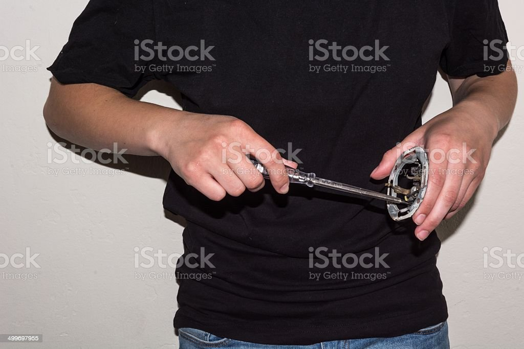Person using a screwdriver on a damaged socket royalty-free stock photo