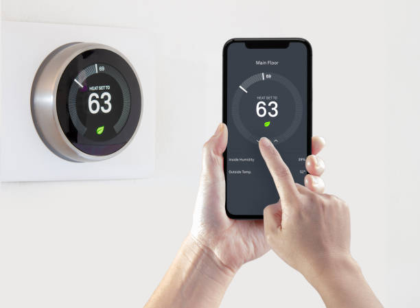 A person using a smart phone application saving energy with a wireless smart thermostat on a white background. A person using a smart phone application saving energy with a wireless smart thermostat on a white background. smart thermostat stock pictures, royalty-free photos & images