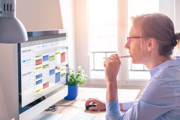 osoba korzystająca z kalendarza na komputerze w celu poprawy zarządzania czasem, efektywnego planowania terminów, wydarzeń, zadań i spotkań, poprawy wydajności, organizowania dni tygodnia i godzin pracy, kobiety biznesu, biura - czas zdjęcia i obrazy z banku zdjęć
