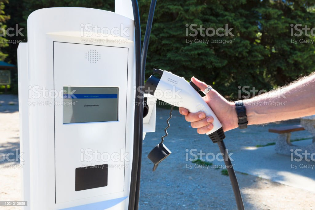 Close up of a person using an electric car public charging station.