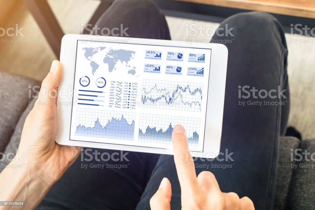Person using financial dashboard on tablet computer screen at home stock photo