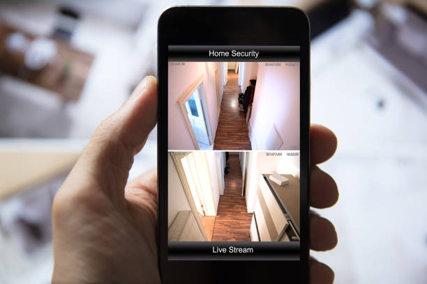 Person Using Home Security System On Mobile Phone stock photo