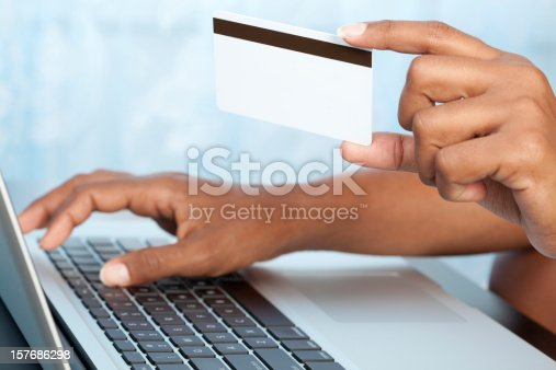 Close up woman's hands typing credit card number on computer.