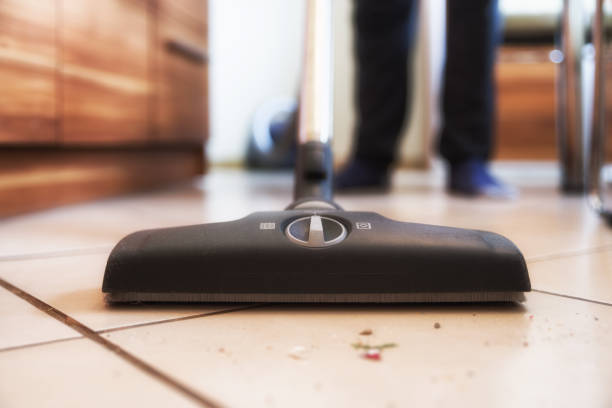Person using vacuum cleanener while cleaning floor at home stock photo