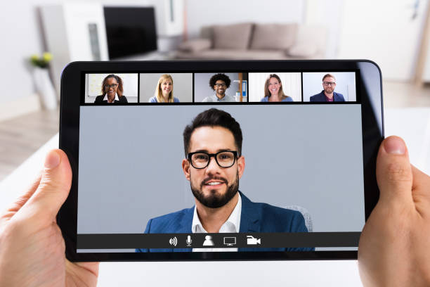 Person Video Conferencing With Doctor On Digital Tablet stock photo