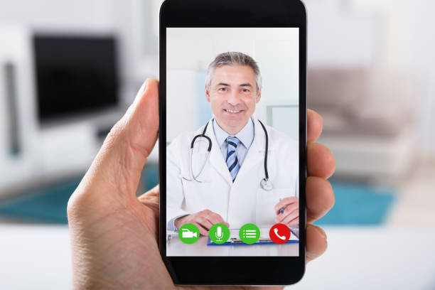 Person Video Conferencing With Doctor On Smartphone stock photo