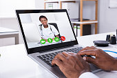 Person Video Conferencing With Female Doctor Through Laptop