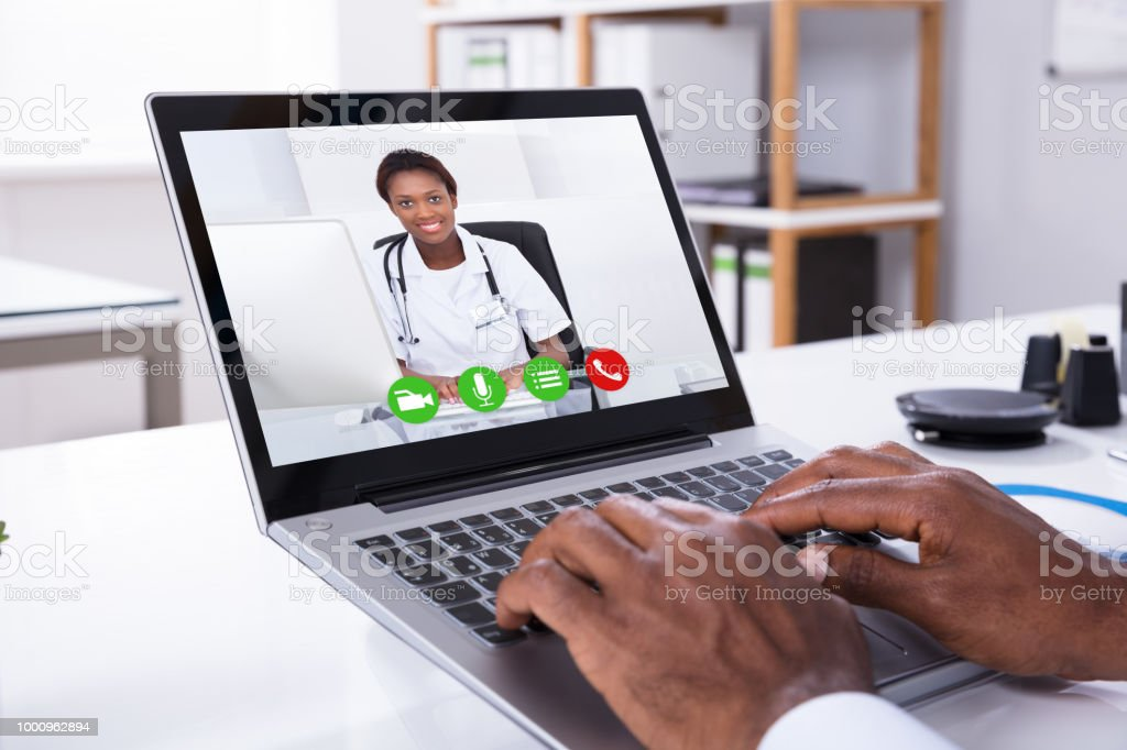 Person Video Conferencing With Female Doctor Through Laptop stock photo