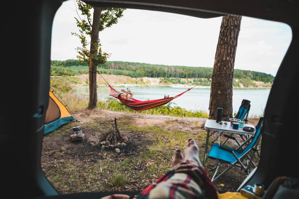 person view couple resting at camping woman laying in hammock with beautiful view of forest lake stock photo