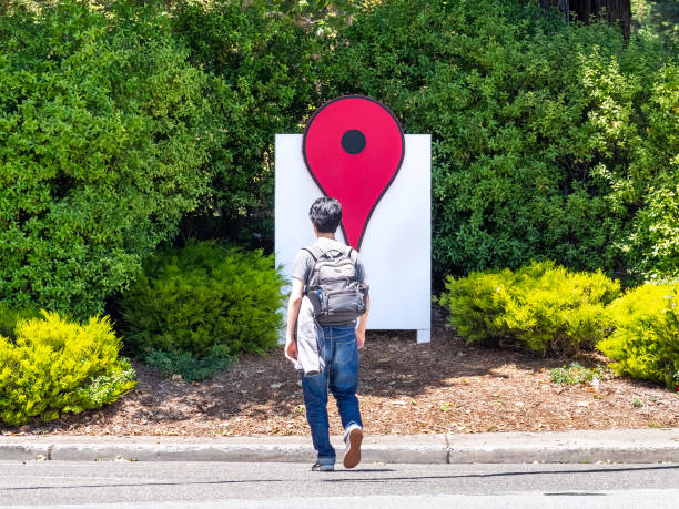 Person walking in front of the Google Maps Icon June 4, 2019 Mountain View / CA / USA - The Google Maps Icon near their offices in the Google campus (Googleplex) in Silicon Valley; employee crossing the street; south San Francisco bay area google stock pictures, royalty-free photos & images