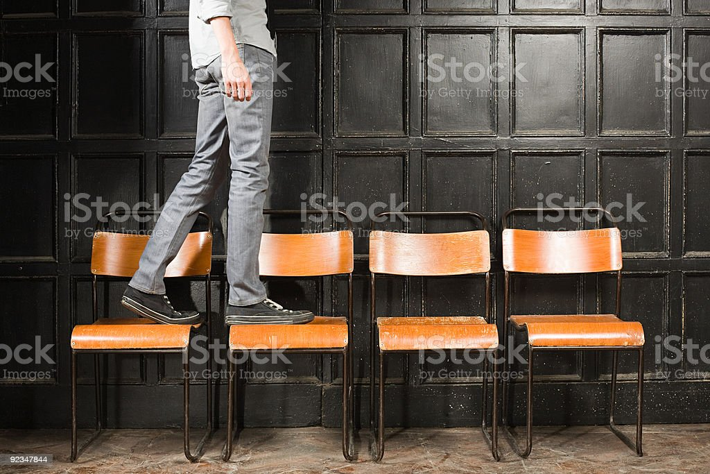Person walking on chairs  Chair Stock Photo