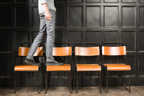 Person Walking On Chairs Stock Photo - Download Image Now