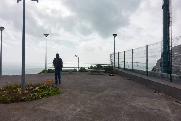 Person walking on Miradouro da Torre viewpoint in Câmara de Lobos, Madeira Person walking on Miradouro da Torre viewpoint in Câmara de Lobos, Madeira ilha da madeira stock pictures, royalty-free photos & images