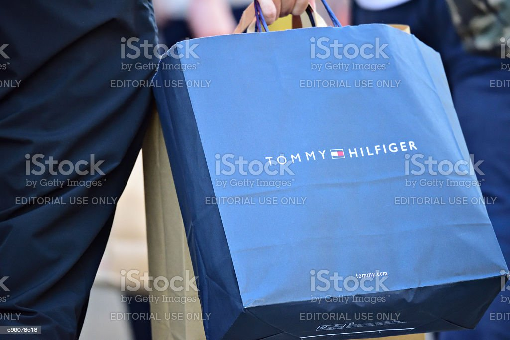 Person walking on sidewalk with Tommy Hilfiger shopping bag royalty-free stock photo