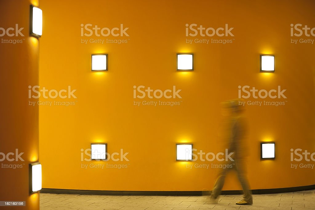 Person Walking Past Illuminated Orange Wall at Night, Blurred Motion royalty-free stock photo