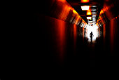 Person walking through a tunnel towards light at end. Accomplishing goal or leaving darkness.
