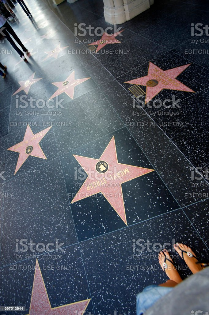 Une personne marche le long de l'Hollywood Walk of Fame. - Photo