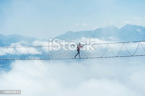 A person walks on a suspended rope bridge in the clouds. Extreme attraction.