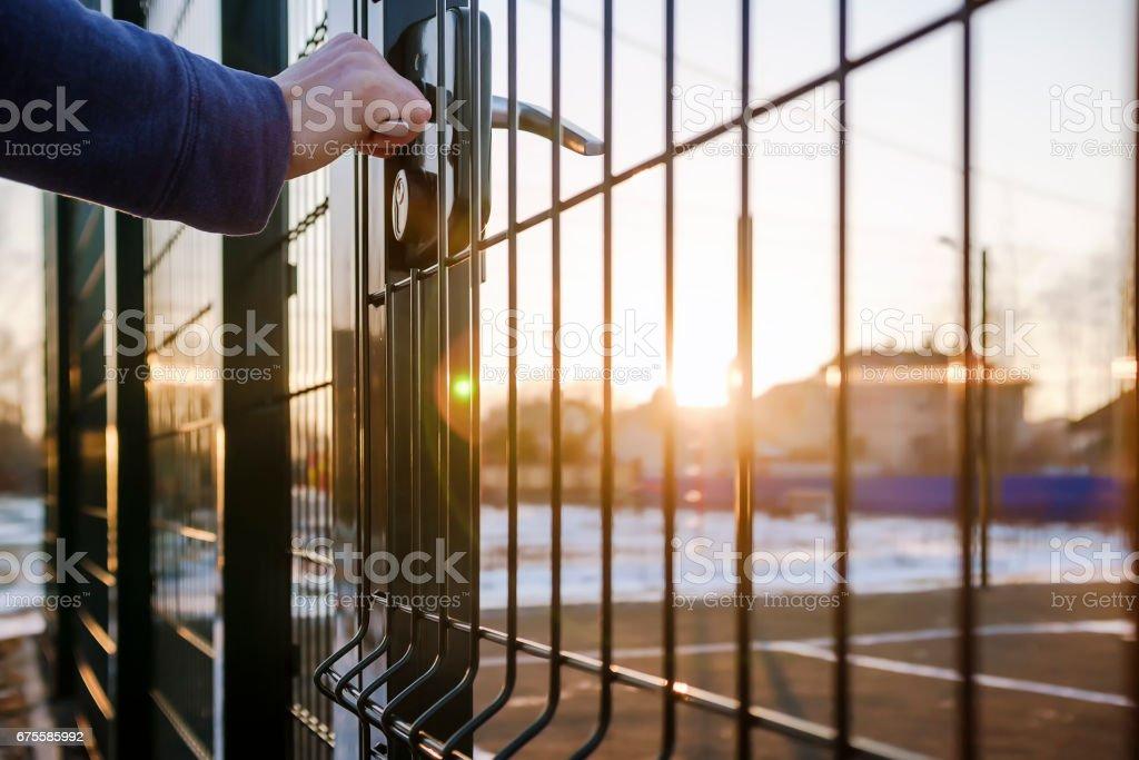 personne veut mettre la main sur le terrain par la petite porte du treillis métallique soudé photo libre de droits