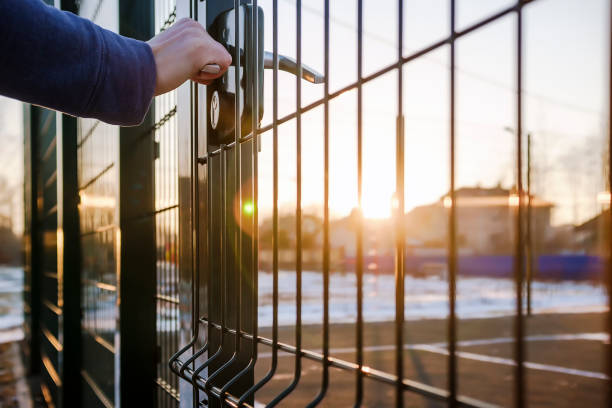 person wants get in on playground through the little gate of welded wire mesh stock photo
