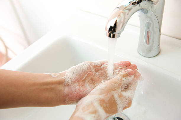 Person washing their hands with lots of soap stock photo