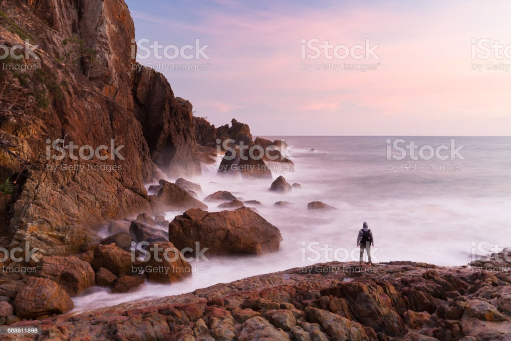 Person Watches Ocean Sunrise at Cliff Base stock photo