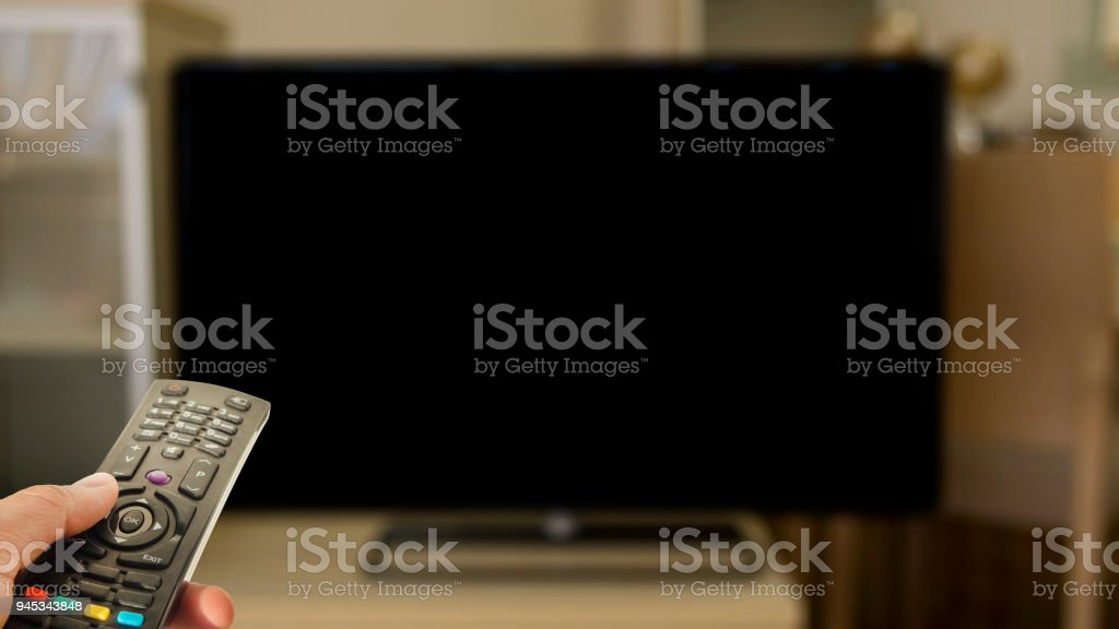 person watching television with control and black blank screen