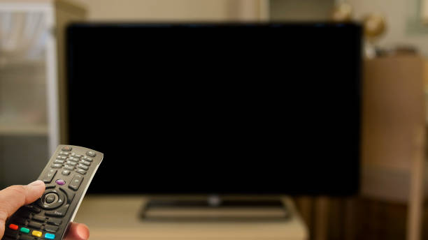 person watching television with control and black blank screen stock photo