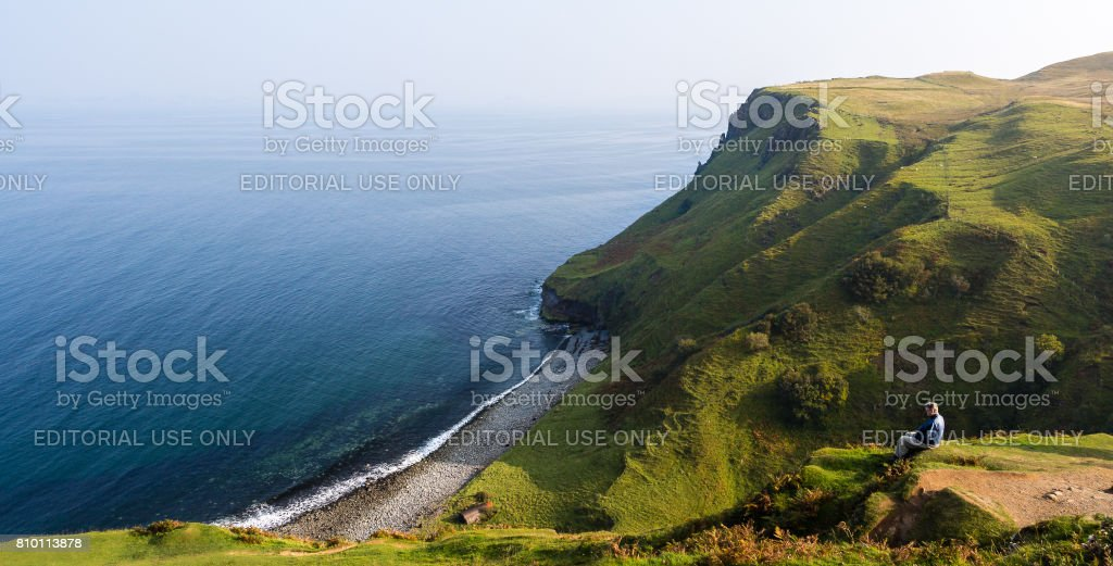 Person watching the sea at Mealt Falls in Skye, Scotland stock photo