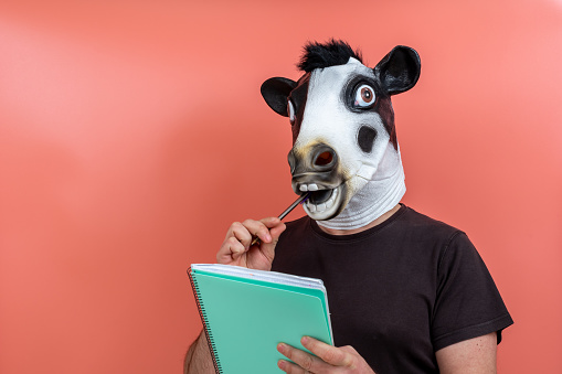 person wearing a cow mask and surgical mask taking notes with a pen on a notepad