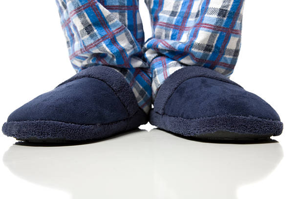 A person wearing a pair of blue slippers with plaid pants stock photo