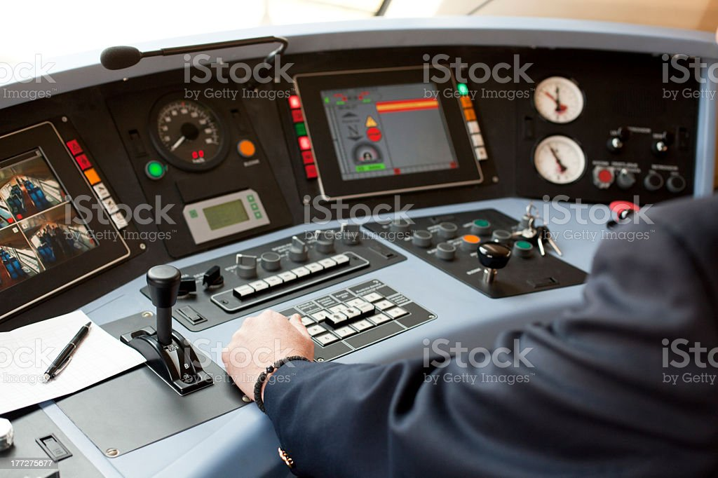 Person wearing blazer with left hand on railroad dashboard stock photo