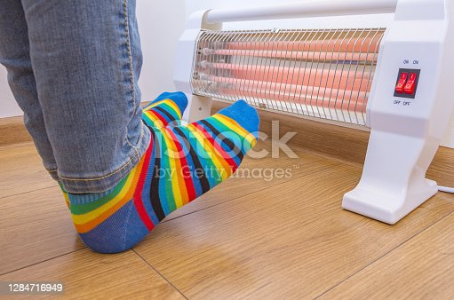 A person wearing bright rainbow-colored socks and warms cold feet near an electric heater. Infrared halogen heater at home.