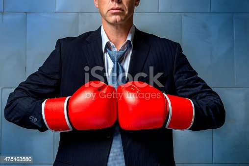464164875 istock photo person wearing business suit and boxing gloves 475463580