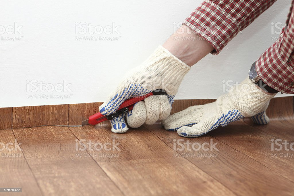 Person wearing gloves cutting linoleum with knife stock photo