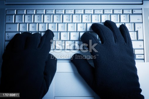 istock A person wearing gloves while on the computer  170169811