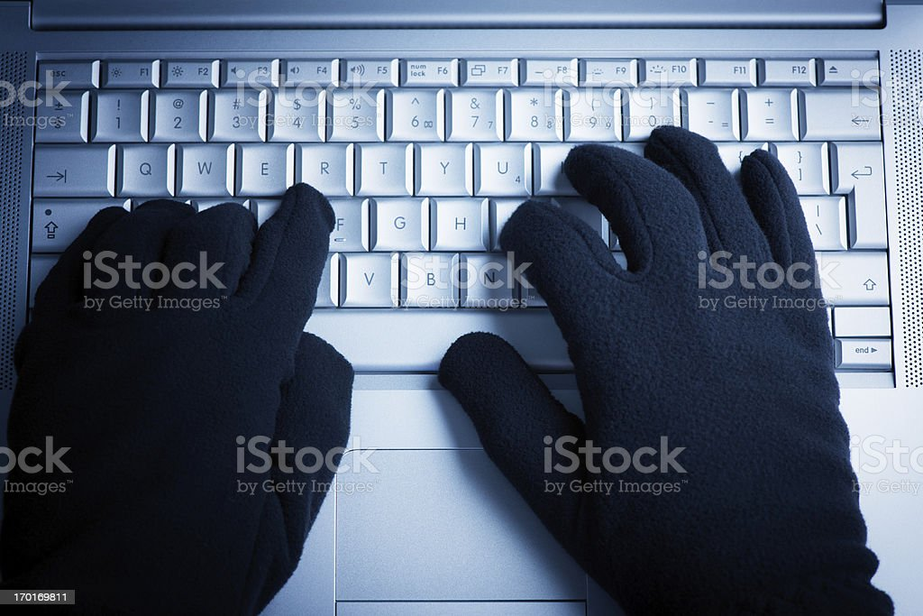 A person wearing gloves while on the computer  stock photo