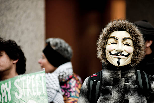 person wearing guy fawkes mask, occupy movement - guy fawkes mask stock photos and pictures
