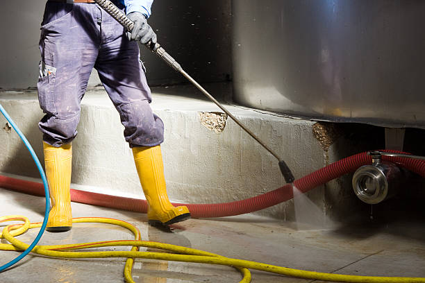 Person wearing yellow wellingtons jet spraying the floor stock photo