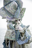 Portrait of white female mask in beautiful creative costume at carnival in Venice, Italy.