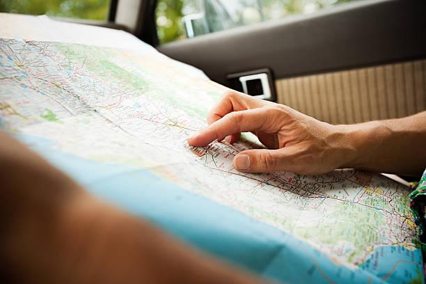 person mit einer karte - karte navigationsinstrument stock-fotos und bilder