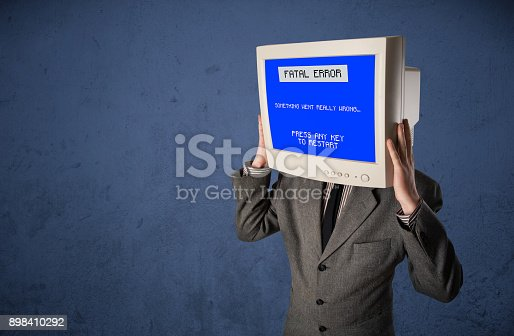 istock Person with a monitor head and fatal error blue screen on the display 898410292