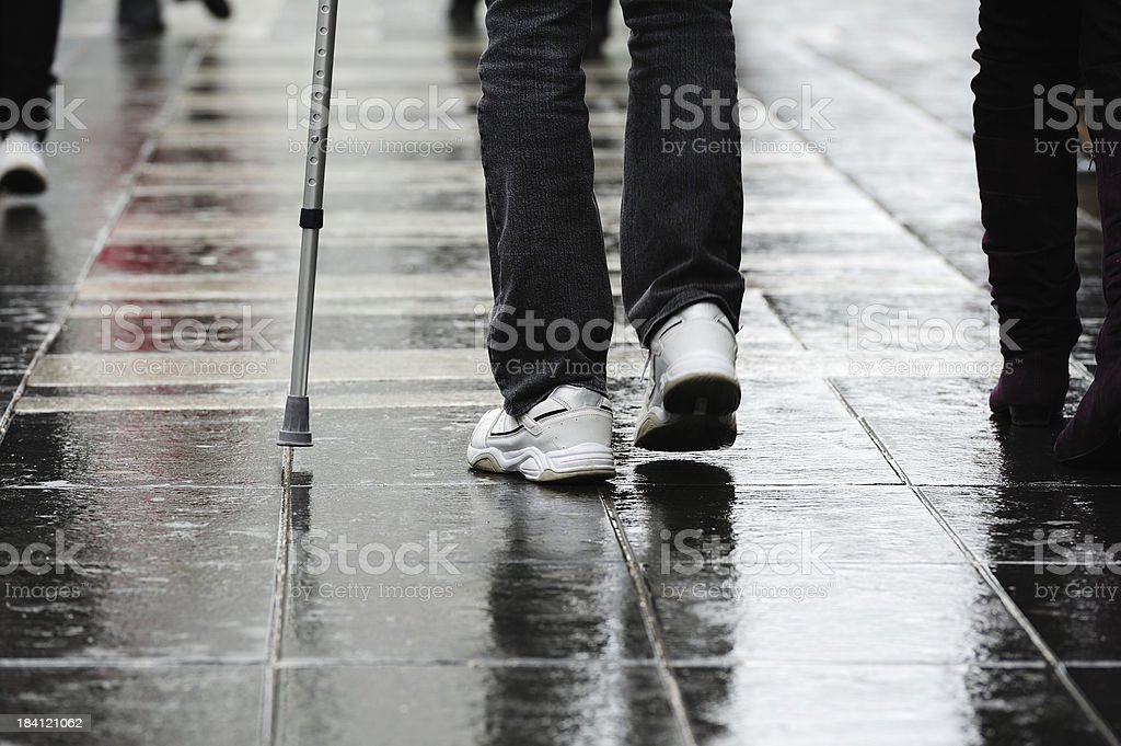 Person with cane crossing rain wet square stock photo