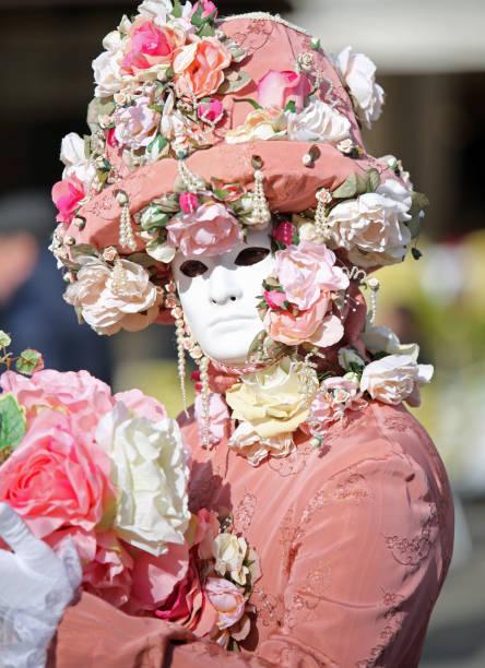 person mit karnevalskleid und weiße maske - rosa camo party stock-fotos und bilder